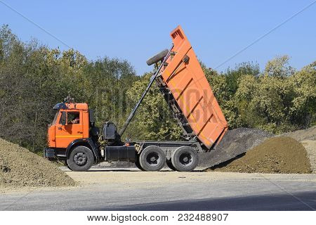 The dump truck unloads rubble. The truck dumped the cargo. Sand and gravel. Construction of roads. poster