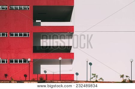 The Facade Of The Modern Building Divided Into Two: One Part Of The Facade Is Red And Has Balconies