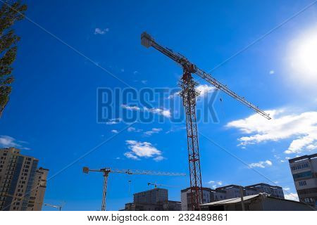 Tower Building Crane Against The Blue Sky And Sun. Construction Of New Buildings With A Crane. Tower