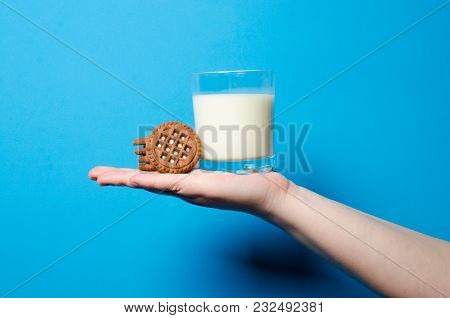 The Girl Is Holding A Brown Biscuit And A Glass With Fresh Natural Milk. The Concept Of Sweet Food A