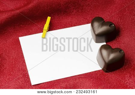 Chocolate Hearts On A Background Of Red Fabric And White Blank Card
