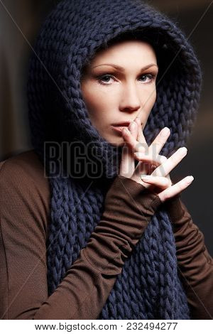 Portrait Of Middle Age Woman In Brown Sweater With Blue Scarf.