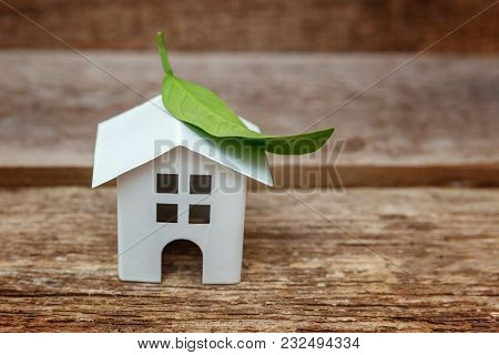 Miniature White Toy Model House With Green Leaves On Wooden Backgdrop. Eco Village, Abstract Environ