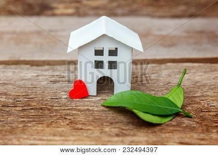 Miniature White Toy Model House With Green Leaves And Red Hearts On Wooden Backgdrop. Eco Village, A