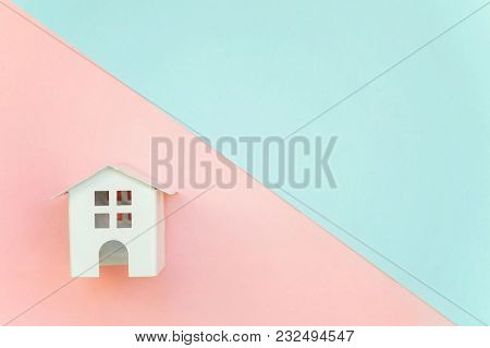 Miniature White Toy House On Pink And Blue Pastel Color Paper Geometric Flat Lay Background. Mortgag