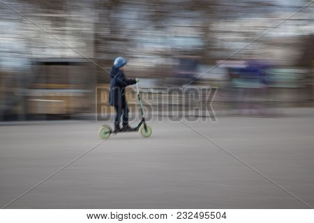 Little Boy Is Riding A Kick Scooter. Heis Looking Away.