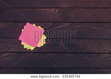 Stack Of Paper Notes On Dark Wooden Desk.