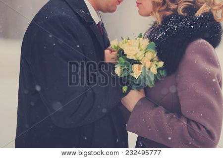 Romantic Winter Day Outdoors. Loving Man And Beautiful Woman With Bouquet Of Yellow Roses Holding Ha
