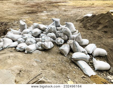 White Sandbags Are Lying On The Ground At The Construction Site.