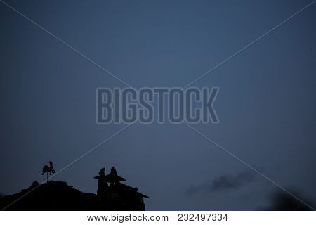 Weathercock Silhouette On The Roof During The Night Next To Chimney In Dolen, Rhodope Mountain, Bulg