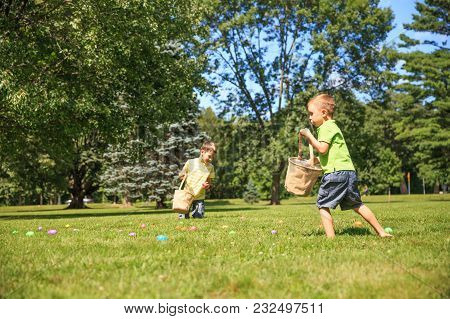 Children Hunt For Easter Eggs. Happy Kids Pick Up Colorful Eggs. The Concept Of Easter Egg Hunt. Cop