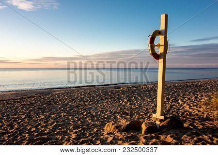 Lifebuoy On A Sandy Beach Of The Baltic Sea In Denmark Near Idestrup During Beautiful Sunrise