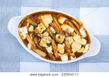 Restaurant Delicious Poutine Meal On Tablecloth Canadian Meal Made With Fries Gravy And Cheese Curds