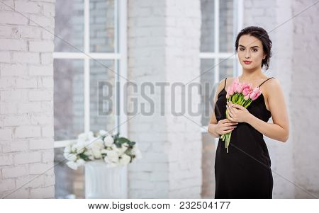 Beautiful Young Woman With Bunch Of Tulips Indoors
