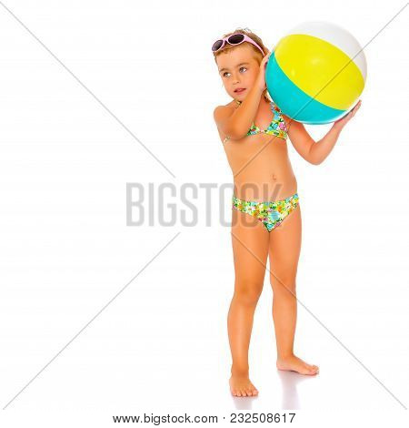 A Little Girl In A Swimsuit Is Playing With A Big Ball. The Concept Of A Family Vacation At Sea, Hap