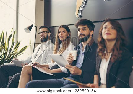 Four Business People On A Meeting In A Modern Conference Room. Focus On The Woman On The Left