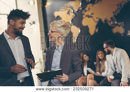 Businessman And Businesswoman Reviewing Contract; Business Team Working In The Background. Focus On