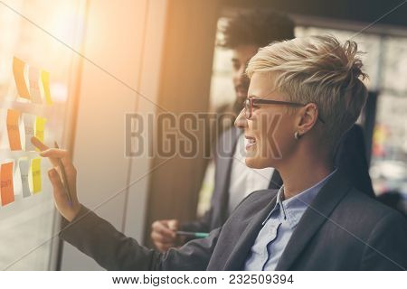Businessman And Businesswoman Brainstorming Using Sticky Notes On A Glass Wall In An Office