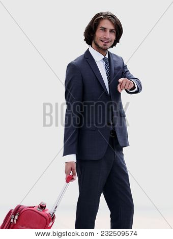 businessman with travel suitcase pointing forward