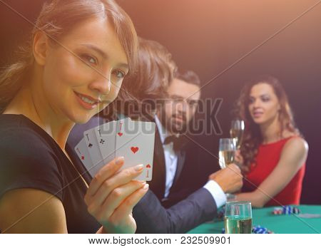 Portrait of the female gambler at the poker table with cards