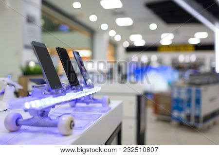 New Mobile Smartphones With Touchscreen, Exposed On Flashing Skateboard In Electronic Store, Digital