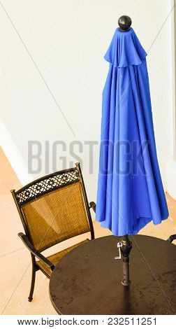 Closed Blue Umbrella On A Table With An Empty Chair On A Patio.