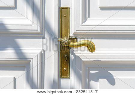 Close Up Of Classic Golden Door Handle On White Door.