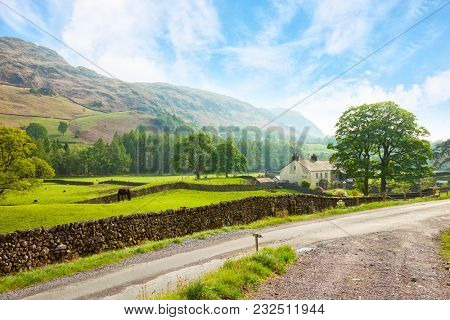 Scenic view of a valley with a  country road in the foreground at the sunny day in Lake District National Park, Cumbria, England, UK.
