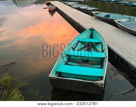 Turquoise Blue Boat Floating On A Lake At Sunset
