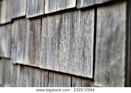 A closeup of grey wooden outdoor shingles on a wall.