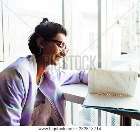 Young Cute Hipster Girl Student Sitting In Cafe With Notebook Reading, Wearing Glasses, Lifestyle Ha