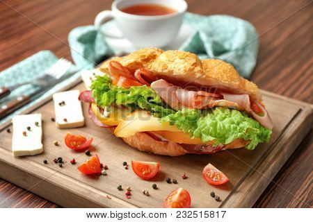 Tasty croissant sandwich on wooden board, closeup
