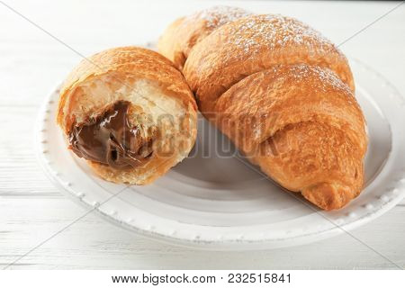 Tasty croissants with chocolate on plate, closeup