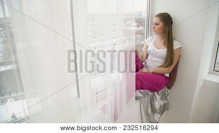 Relaxing Leisure. Young Pensive Thoughtful Teen Girl Sitting On The Windowsill And Looking Out Of Th