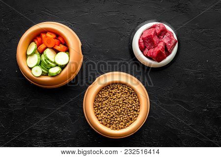 Dry Pet Food With Natural Ingredients. Raw Meat, Vegetables Zucchini And Carrot On Black Table Backg