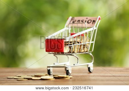 Shopping cart and coins on table against blurred background. Pension planning concept