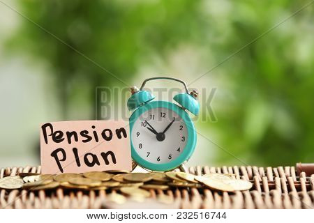 Coins and alarm clock on wicker surface against blurred background. Time for pension planning