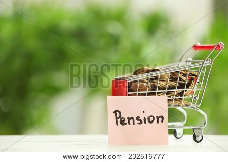 Shopping cart with coins on blurred background. Pension planning concept