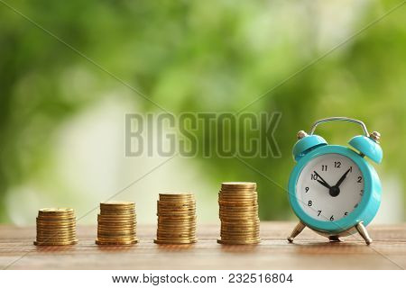 Composition with stacks of coins and alarm clock on blurred background. Time for pension planning