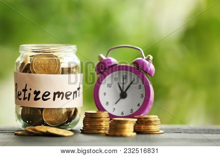 Coins in glass jar and alarm clock on blurred  background. Time for pension planning