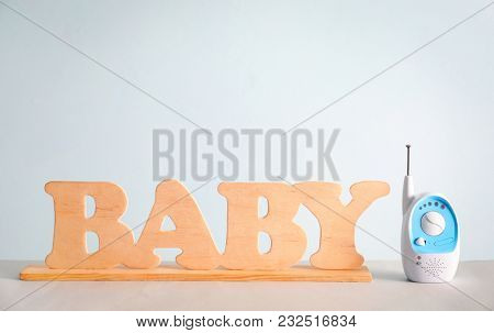 Baby monitor and wooden letters on table against color background