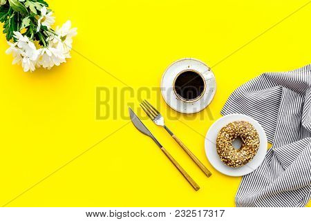 Modern Breakfast Desing With Sweet Donut, Cup Of Coffee And Flowers On Woman Yellow Desk Background