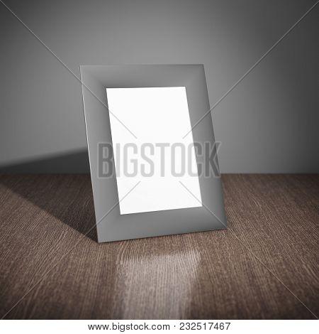 Blank aluminum photo frame on wooden table. 3D illustration.