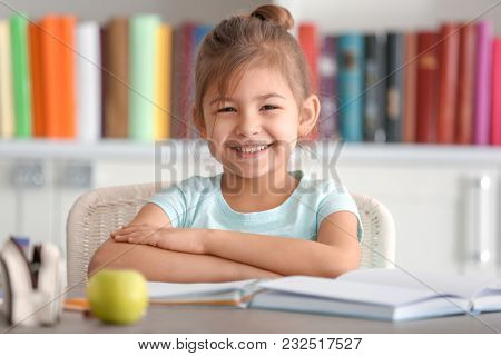 Cute little girl doing homework indoors