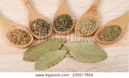 Wooden Spoons With Traditional Italian Herbs For Cooking On A Light Wood Table.