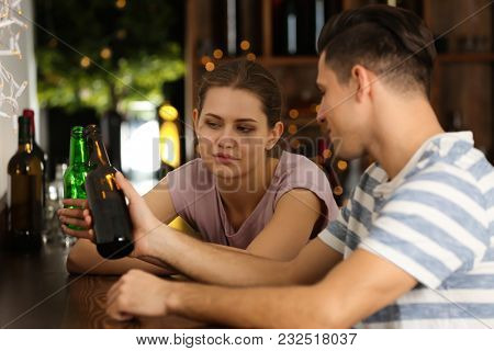Young couple drinking in bar. Alcoholism problem