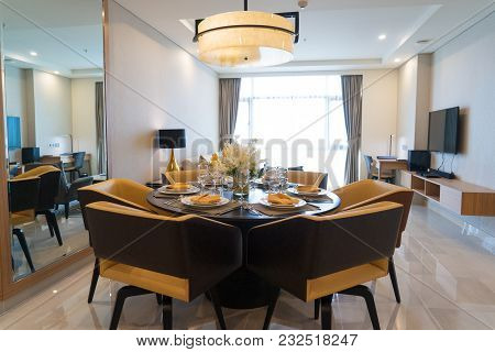 Modern Dining Room With Flower Arrangement And Mirror. Futuristic Chandelier Above Setting Table Wit