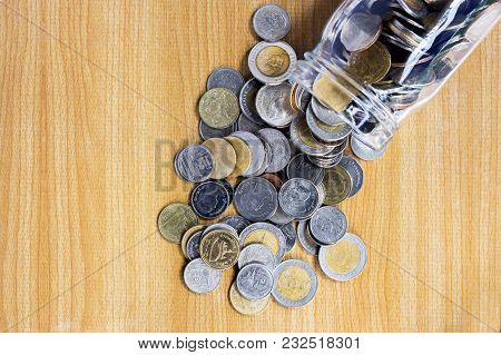 A Pile Of Coins With A Glass Jar On The Wooden Table.  Saving Money Concept For Education Or Investm