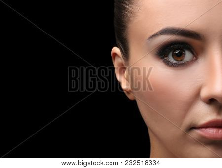 Beautiful young woman with eyelash extensions on dark background, closeup