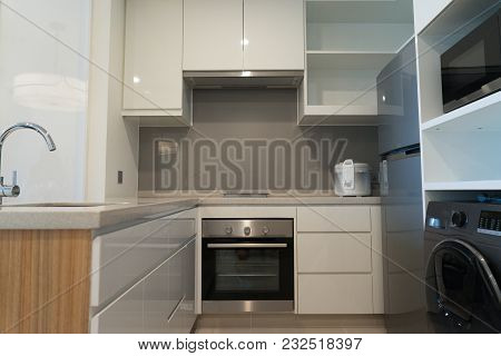 Modern Kitchen With Minimalist Design. Small Kitchen Set Equipped With Appliances Such Like Freezer,